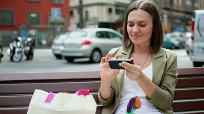 stock-footage-young-woman-using-smartphone-in-the-city